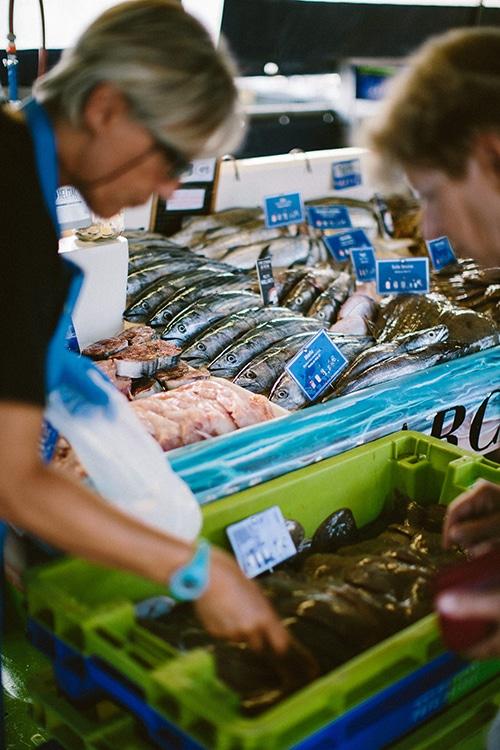 Twee mensen zoeken vis uit op de vismarkt in Capbreton.