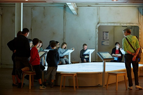 Mensen bekijken een tentoonstelling in Escal'Atlantic, een museum in Saint-Nazaire.