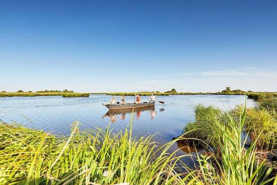 Een bootje vaart op een meer in natuurpark Briere in Frankrijk.