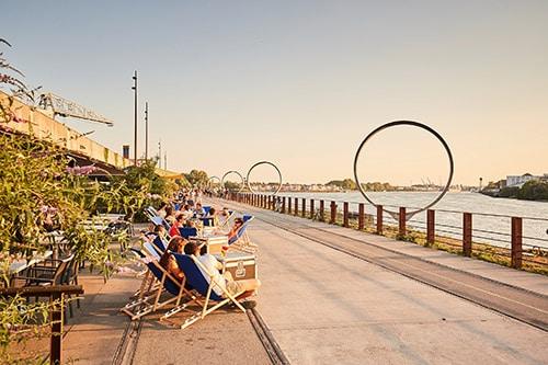 Mensen zitten in strandstoelen aan de rand van het water in Île de Nantes.