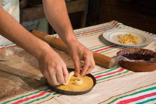 De banketbakker van het Musée du Gâteau Basque versiert de taart met het traditionele Baskische kruis.