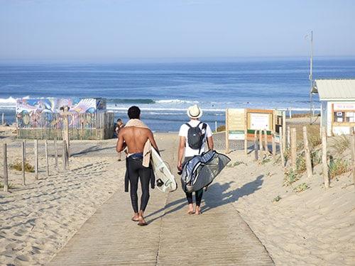 Twee surfers lopen richting het strand van Le Porge in Frankrijk.