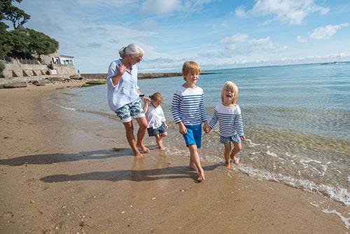 Een vrouw loopt met 3 kinderen op het strand van Île de Noirmoutier.zeau