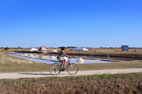 Een vrouw fietst op Île de Noirmoutier aan de Atlantische Kust van Frankrijk.