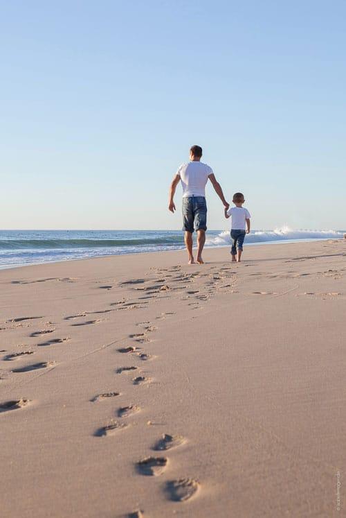 Man en kind wandelen over het strand van Soulac aan de Atlantisch e Kust van Frankrijk.