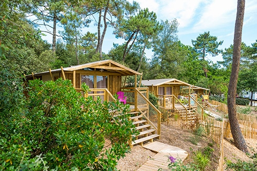 Twee houten accommodaties op een camping in Frankrijk.