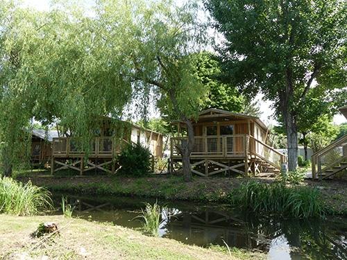 Twee houten huizen op een camping aan de Atlantische Kust van Frankrijk.