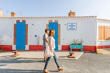 Twee mensen lopen langs een huis in Saint-Gilles-Crouix-de-Vie in Frankrijk.