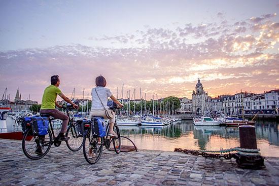 Twee fietsers bewonderen de zonsondergang in La Rochelle