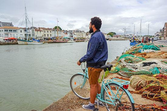 Een fietser kijkt uit over de haven van Pornic aan de Atlantische Kust van Frankrijk.