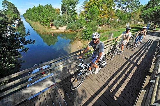 Fietsers steken een kleine houten brug in Les Landes over.