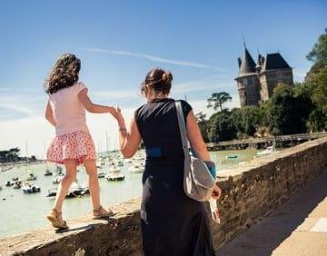 Een vrouw helpt een kind over een muurtje lopen langs de zee in Pornic.