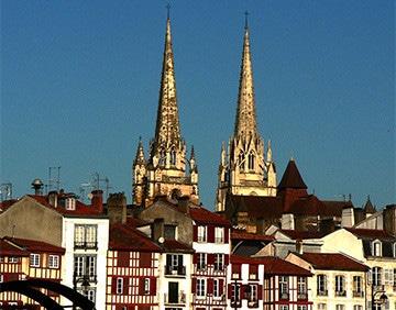 Een straat in Bayonne met twee torens op de achtergrond.