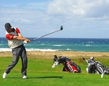 Een man is aan het golfen met de zee op de achtergrond in Moliets.