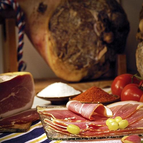 Gesneden rauwe ham met een hele ham op de achtergrond in Frans-Baskenland.