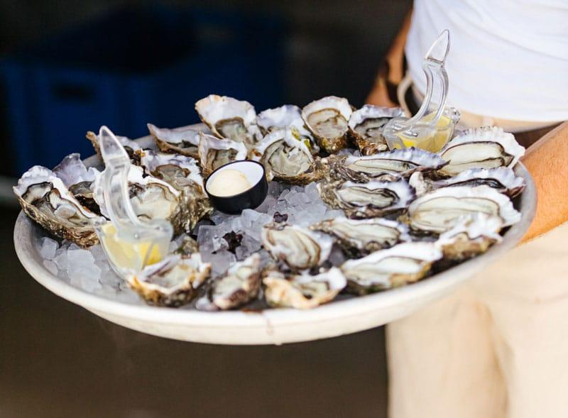 Een man draagt een schaal met oesters.