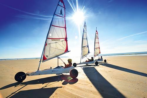 Drie mensen blowkarten op het strand van de Atlantische Kust in Frankrijk.