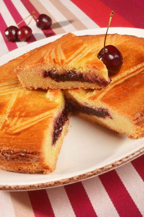 De gâteau basque met een stuk eruit gesneden op een bord.