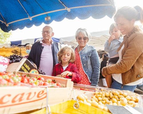 Vijf mensen bij een kraam op een weekmarkt in Frankrijk.