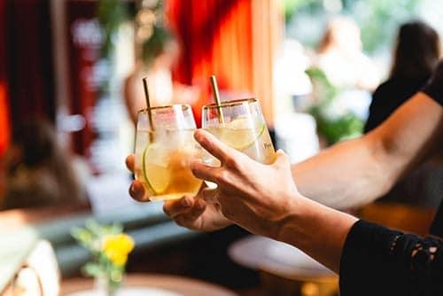Twee mensen proosten met een cocktail met pineau des Charentes.